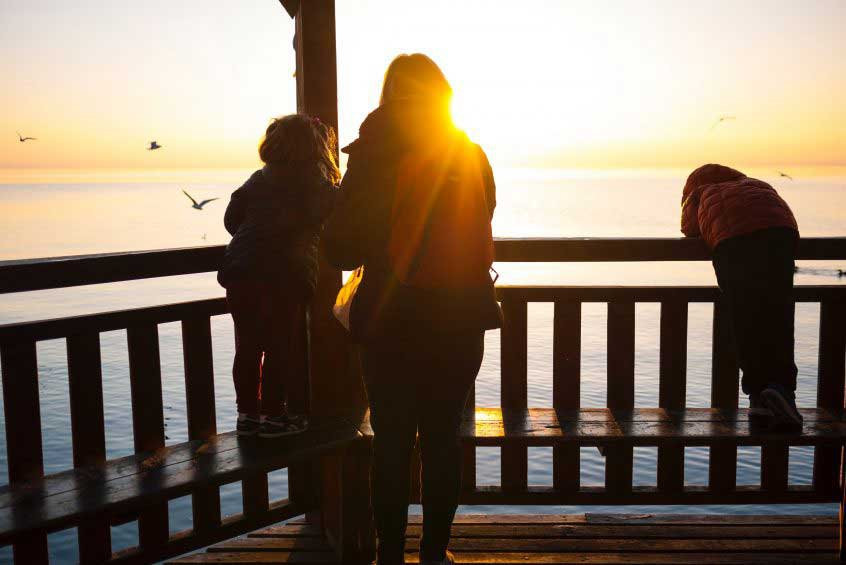 family looking over ocean at sunset - grant trevithick dallas real estate investor academy