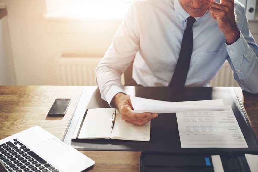 businessman at office desk reading - grant trevithick dallas tx real estate investor